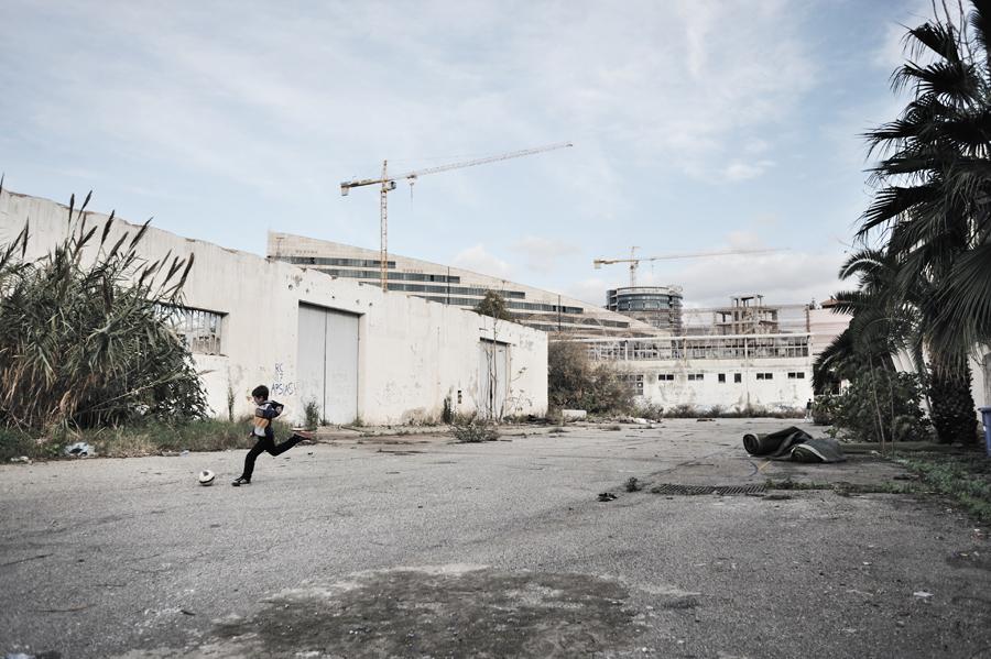 San Giorgio Extra, quartiere a sud della città. Un bambino gioca a pallone nell'area di una vecchia fabbrica abbandonata. Alle spalle, l'imponente Palazzo di Giustizia, grande opera al momento incompiuta. Nel 2013 la Bentini Spa, ditta vincitrice della gara d'appalto, abbandona il cantiere dopo 8 anni di lavori.